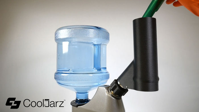 Drop your container with the shrink sleeve through the top of the steam head and allow it to drop into your catch basin